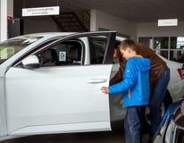 有孩子的一个人通过门户开放主义学习一辆新的汽车的内部 免版税库存图片