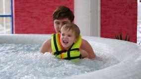 有孩子的一个年轻父亲在温泉水池游泳 放松和乐趣在水池 免版税库存照片