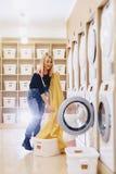 有孩子的一名妇女在洗衣店投入板料 免版税库存图片
