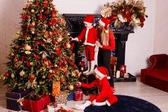 有孩子的一年轻女人装饰圣诞树 库存图片