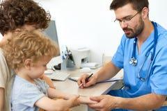 有孩子的儿科医生在办公室 图库摄影