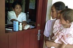 有孩子的印地安母亲得到疗程 免版税库存照片