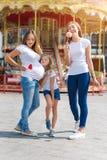有孩子的同性女同性恋的家庭步行的在游乐园 有被领养的孩子的,愉快的家庭女同性恋者母亲 免版税库存照片