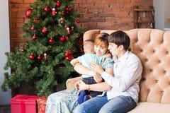 有孩子的圣诞节家庭 愉快的微笑的在家庆祝新年的父母和孩子 圣诞节我的投资组合结构树向量版本 库存图片