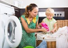 有孩子的妇女在洗衣机附近 图库摄影