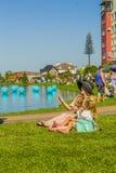 有孩子的妇女坐草在湖附近 库存照片