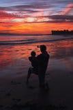 有孩子的妇女拍看往Anacapa海岛,维特纳,加利福尼亚,美国的紫色和橙色日落的照片 免版税图库摄影