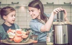 有孩子的妈妈在厨房准备新鲜的汁液 免版税库存照片