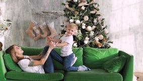 有孩子的妈妈在圣诞树的背景的沙发使用 圣诞节内部 影视素材