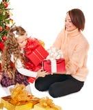 有孩子的家庭在圣诞树附近打开礼物盒。 免版税库存图片
