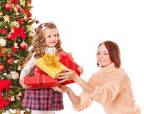 有孩子的家庭在圣诞树附近打开礼物盒。 免版税图库摄影