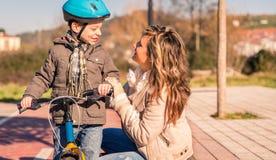 有孩子的少妇在自行车在晴天 免版税库存照片