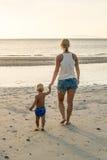 有孩子的少妇去海 免版税图库摄影