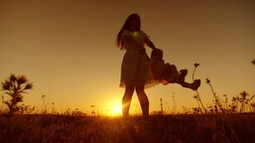 有孩子的年轻和美丽的母亲旋转在飞行中在金黄太阳日落并且笑 慢的行动 影视素材
