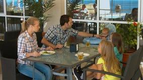 有孩子的愉快的家庭吃午餐在咖啡馆 库存图片