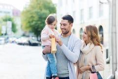 有孩子的愉快的家庭和购物袋在城市 免版税库存照片