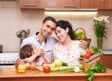 有孩子的愉快的家庭家庭厨房内部的用新鲜的水果和蔬菜,孕妇,健康食物概念 库存图片