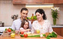 有孩子的愉快的家庭家庭厨房内部的用新鲜的水果和蔬菜,孕妇,健康食物概念 免版税库存图片