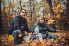 有孩子的愉快的家庭步行的在公园 免版税库存图片