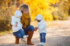 有孩子的愉快的母亲在秋天公园 图库摄影