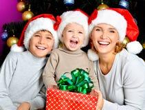 有孩子的愉快的母亲拿着新年礼物 免版税图库摄影
