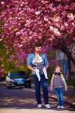 有孩子的愉快的父亲在步行在春天城市,小型航空母舰,父亲事假 库存照片