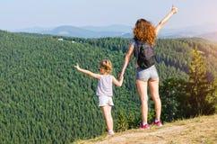 有孩子的旅客母亲在户外高山顶部,看在美好的风景,自由空间 免版税库存照片