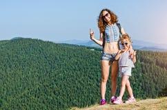 有孩子的旅客母亲在户外高山顶部,看在美好的风景 免版税库存图片
