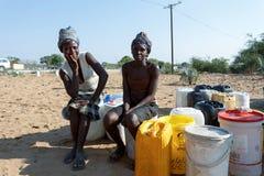 有孩子的未认出的纳米比亚妇女在与dri的公开坦克附近 免版税库存图片