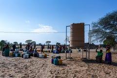 有孩子的未认出的纳米比亚妇女在与dri的公开坦克附近 图库摄影