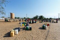 有孩子的未认出的纳米比亚妇女在与dri的公开坦克附近 免版税库存照片