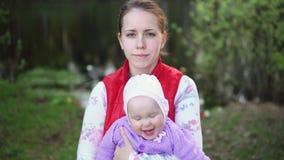有孩子的母亲在公园走靠近湖在日落 股票录像