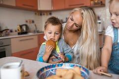 有孩子的母亲在厨房,儿子吃一个曲奇饼 免版税库存照片