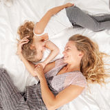 有孩子的母亲在床上 免版税库存图片