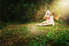 有孩子的母亲在童话森林里 库存图片