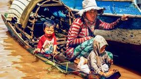 有孩子的母亲在Tonle Sap湖的小船的 免版税库存照片