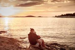 有孩子的母亲坐海滩,观看的日落 库存照片