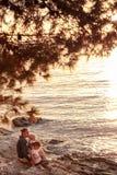 有孩子的母亲坐海滩,观看的日落 免版税库存照片