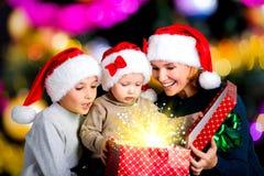 有孩子的母亲打开有圣诞节礼物的箱子 库存照片