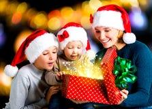 有孩子的母亲打开有礼物的箱子在圣诞节h 免版税库存图片