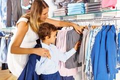 有孩子的母亲搜寻衣裳,当购物时 免版税库存照片