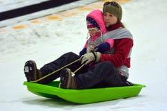 有孩子的母亲雪的滑了幻灯片下坡 库存图片