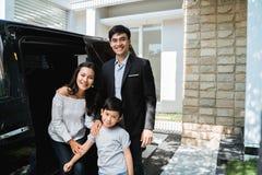 有孩子的父母在他们汽车微笑前面 免版税库存照片