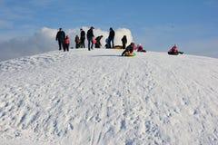 有孩子的爸爸滑下来雪小山周末 免版税图库摄影