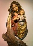 有孩子的玛丹娜在一个木词根雕刻了 库存照片