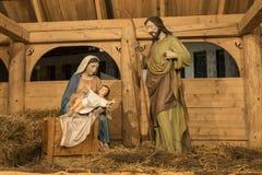 有孩子的耶稣,父亲约瑟夫和圣母玛丽亚圣诞节小儿床 免版税库存图片