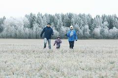 有孩子的年轻家庭在冬天领域走 图库摄影