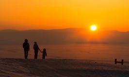 有孩子的年轻家庭,握手,观看的日落,冬天 免版税库存照片