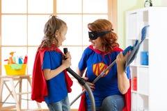 有孩子洁净室的愉快的妇女和获得一个乐趣 一起使用母亲和儿童的女孩 在超级英雄服装的家庭 免版税库存图片