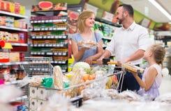 有孩子购物的高兴的父母在大型超级市场 库存照片